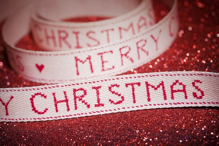 vintage-styled Merry Christmas ribbon and glitter background. Stock Photo