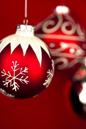 Three Christmas Tree Ornaments on red Background