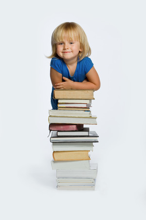 Young girl behind a stack of books.