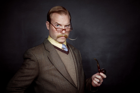 Eccentric male with pipe in vintage clothing.