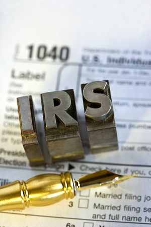 IRS forms with a pen and printers blocks.