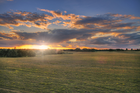 Open fields at sunset. Beautiful rural landscape with vibrant clouds and vast fields. Фото со стока