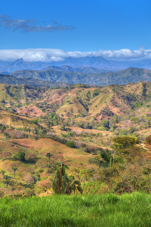 Colorful landscape of Panama in Central America. Green grass and tropical trees with cloud covered mountains in the background.