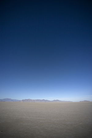 Photo of salt flats and some mountains in the background.