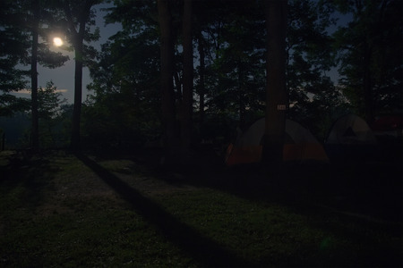 Night time campsite with full moon rising and casting shadows on the ground.