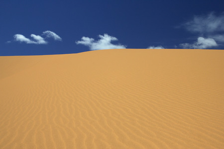 Sand dune and blue sky, desert landscape. Фото со стока