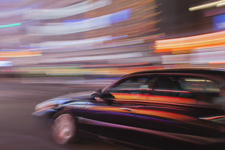 Abstract Image of a town car in motion with blurred city lights in the background.