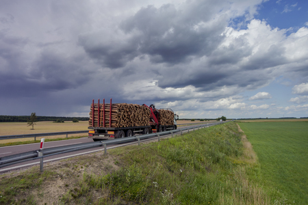 A truck carrying a payload of cut timber on a rural road. Stock Photo