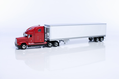 Miniature model of a red 18 wheeler truck and trailor