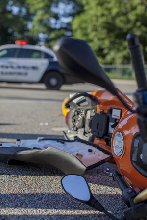 Detail stock photo of a motorcycle crash scene with police vehicle in the background.
