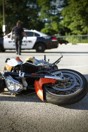 Detail of a motorcycle accident with squad car in the background. Фото со стока