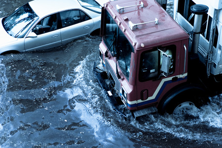 Flooded streets showing one car stranded and a truck driving through the water.