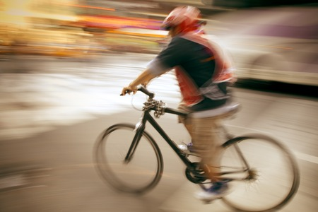 Abstract photo of a bike courier on a busy street. Фото со стока