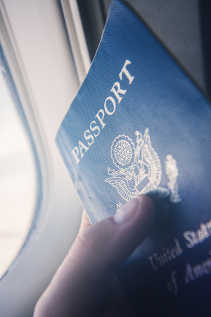 First person point of view stock photo of a man holding American Passport while flying in an airplane. Фото со стока