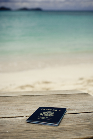 A shot of a Passport on a wooden table at a beach.