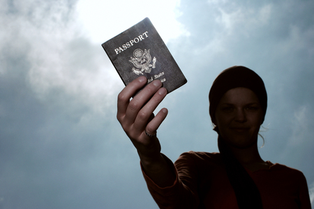 a woman holding a us passport.