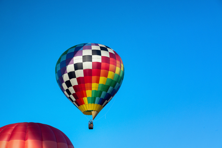 Colorful hot air balloon taking flight on a clear day.