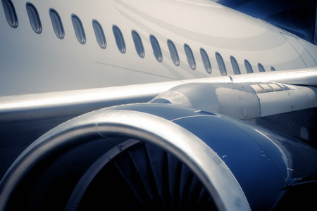 Detail of airplane, showing engine, part of the wind and main fuselage. Soft light. Stock Photo
