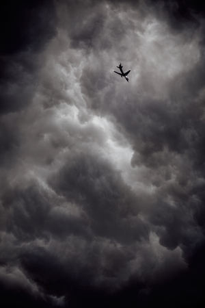 Heavy storm clouds with airplane.