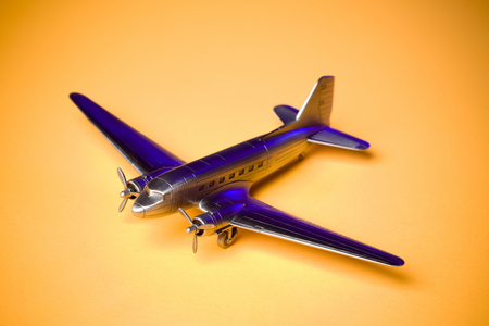 Retro airplane model on yellow background.
