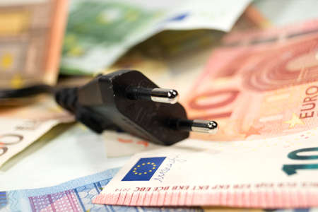 energy suppliers: Power plug and cash Stock Photo