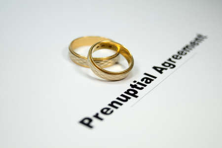 A prenuptial agreement and wedding rings Stock Photo