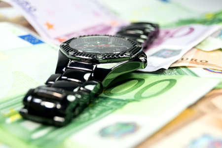 wristwatch: A wristwatch and cash Stock Photo