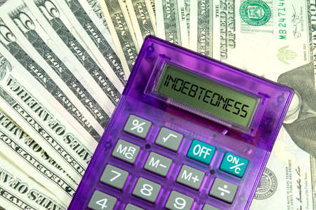 investigated: indebtedness word by calculator Stock Photo