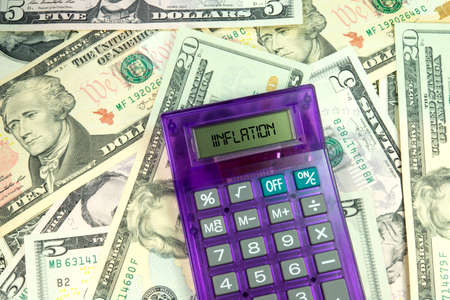 budgetary: Calculator with inflation word on dollar bills Stock Photo