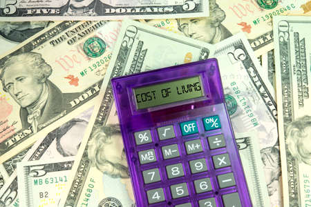 budgetary: Calculator with Cost Of Living word on dollar bills Stock Photo