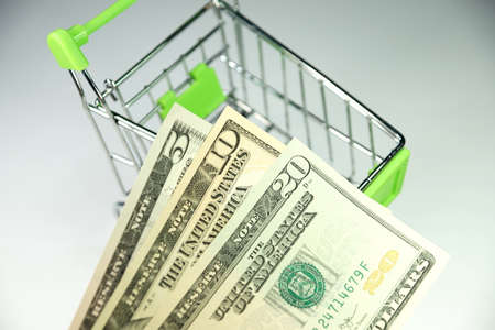 hard sell: Shopping cart and money Stock Photo
