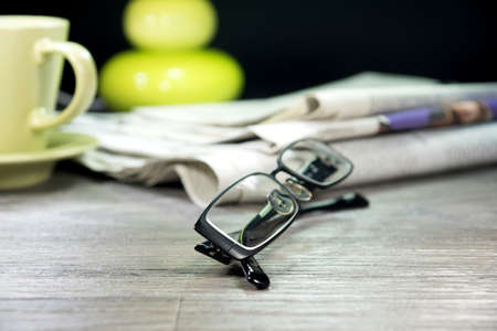 Newspaper, glasses and cup of coffee