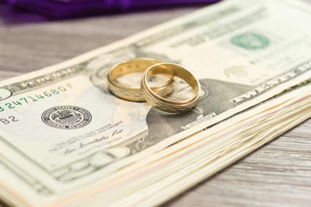 Dollar bills and two wedding rings