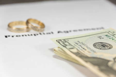 A marriage contract, dollar bills and wedding rings