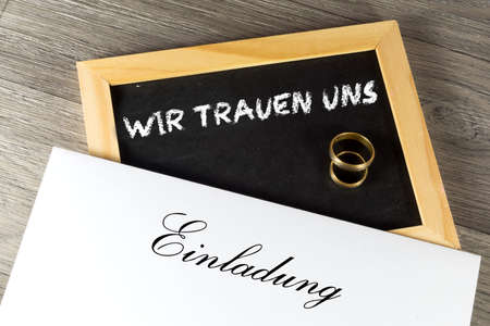 Wedding invitation and wedding rings Stock Photo