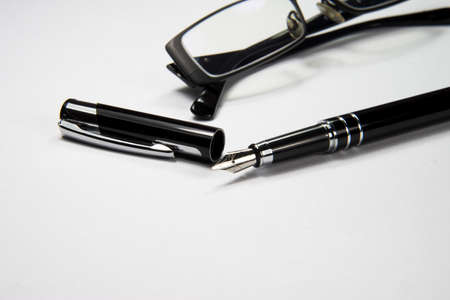 Pen and glasses on a piece of paper