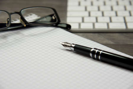 Keyboard, glasses, pen and empty notebook