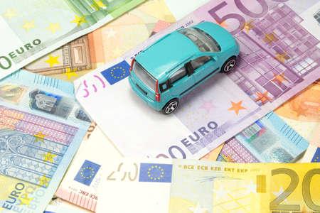 Une voiture et plusieurs factures en euros Banque d'images - 72689075