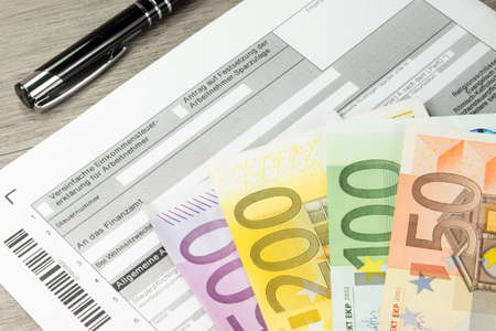 A German form for tax purposes and many euro bills Archivio Fotografico