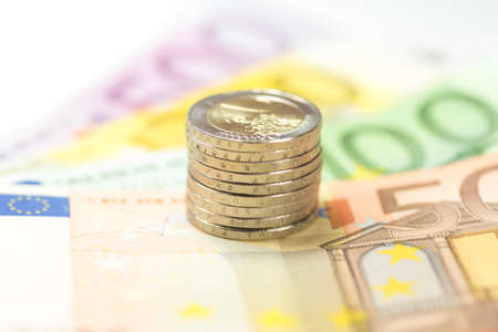 Many euro banknotes and coins Stock Photo