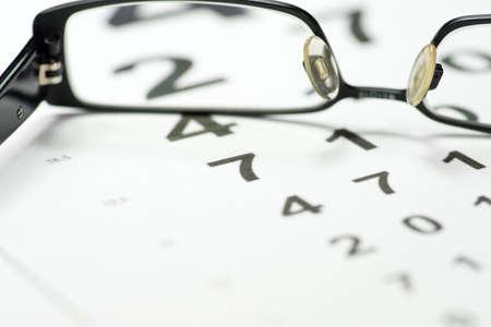 examen de la vista: Glasses and a vision test with an eye doctor Foto de archivo