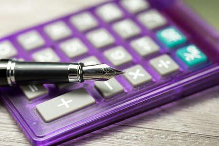 A fountain pen and a calculator Imagens