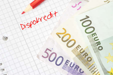 Euro bills and a notepad with the word dispocredit Imagens