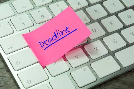 A keyboard and a note with the word Deadline Stock Photo