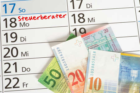 A calendar with an appointment with the tax consultant and many Swiss franc banknotes Stock Photo
