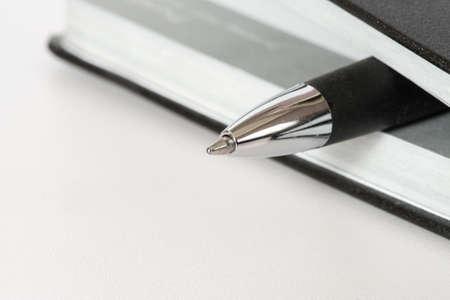 A notebook or calendar and a pen