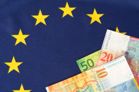Flag of the European Union EU and Swiss Franc banknotes