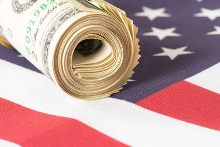Flag of USA and a money roll with dollar bills