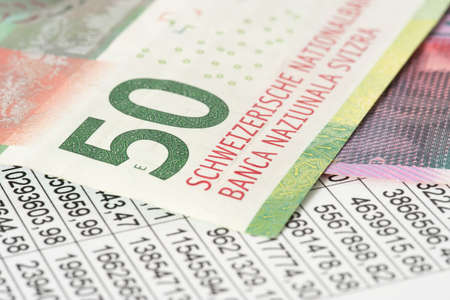 A spreadsheet and banknotes Swiss francs Stockfoto - 96242064