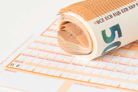A form for a bank transfer and euro banknotes